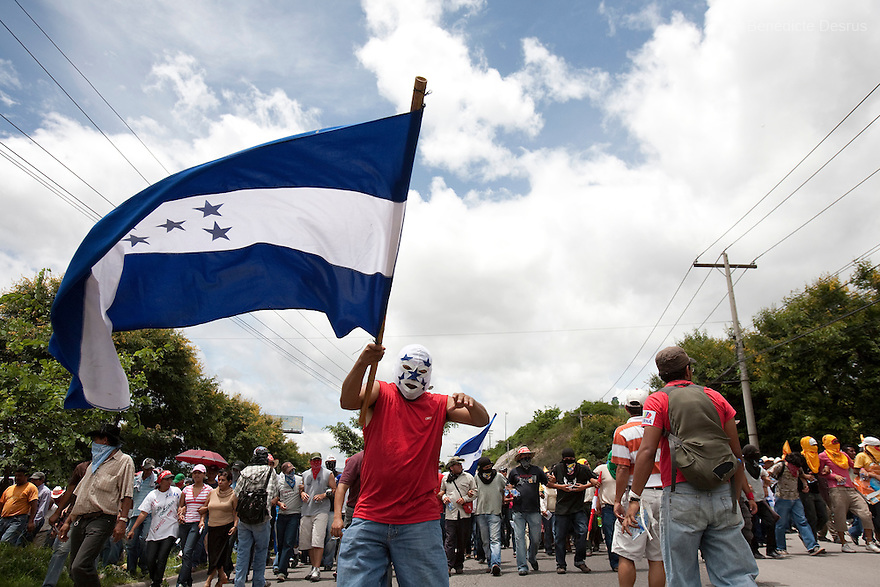 5 July 2009 - Tegucigalpa, Honduras - A supporter of Honduras' ousted President Manuel Zelaya waves a Honduran flag during a march towards the international airport in Tegucigalpa to greet the return of ousted Honduran President Manuel Zelaya. Zelaya turned back from an attempted return home on Sunday after soldiers clashed with his supporters as he tried to land, fueling tensions over the coup that toppled him. Photo credit: Benedicte Desrus