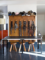 A school coat rack stores riding hats and harnesses; all other furniture - the steel, wood and slate table, a small marble and bronze pillar, Bohemian glass candle holder and white-painted bronze standard lamp - is by Eric Schmitt
