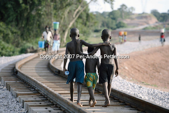 DONDO, ANGOLA APRIL 3: Boys walk along the newly put railway tracks on April 3, 2007 in Dondo, about 200 kilometers outside Luanda, Angola. Hundreds of Chinese workers are working here to put the new tracks. Chinese companies are building and upgrading two different railways in Angola, and this part is about 500 kilometers long. All the special equipment has been shipped from China and hundreds of workers live in military style road camps. They are moved as the tracks are laid down. Tens of thousands of Chinese has come to Africa the last years to work in infrastructure projects and businesses. Chinese companies are often the lowest bidders for contracts, pricing out the more expensive European companies. The Chinese people often live where they work and rarely interact with the local population. Most Chinese don't speak English and they are mostly staying in the compounds cooking their Chinese food. .(Photo by Per-Anders Pettersson).