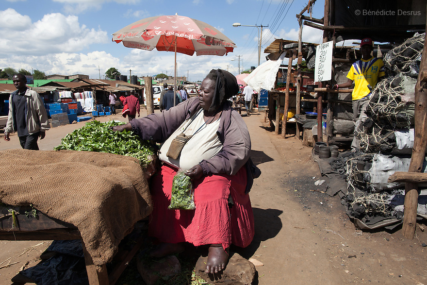 """""""Mama Safi"""" sells vegetables in the street in front of her home inKawangware slum in Nairobi, Kenya on December 8, 2012. Susan Kalai aka """"Mama Safi"""" is a 53 year old Kenyan woman with severe morbid obesity living inKawangware slum in Nairobi, Kenya. Shelives on less than $1 USD a day, selling vegetables and fried potatoes in the street in front of her house. She has 7 children, the youngest one is 9 yearsold. She suffersfrom several obesity-related diseases. She can't walk, has a lot of pain in her legs and back and also has difficulties to breathe. She says """"I was born big. I was always like this.Both my parents and my sister are big too. So for me it's normal. Nothing is wrong with me"""".She has no knowledgeabout obesity and she can't go to the doctor to get treated because she has no money to pay for it. She is afraid to die of a heart attack. Although large parts of Africa areplaguedwith malnutrition, the continent must now also deal with another problem:obesity.Obesity is fast becoming a serious problem in Kenya and even the poorest are now being affected. Obesity rates are climbing around the world and they are rising faster in developing countries than in developed ones. (Photo by Benedicte Desrus)"""