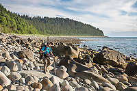Hiker walks on the boulders of a rocky beach near Cape Fairweather in the Gulf of Alaska, Pacific ocean coast, Glacier Bay National Park, Southeast, Alaska.