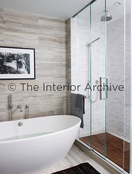 The walls and floor of the bathroom are lined in travertine and the shower is tiled with Cipollino tumbled marble