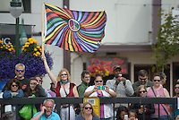 Lesa Hollen of the University of Alaska Chorus waves a flag in honor of the Orlando shooting victims during the 2016 Downtown Summer Solstice Festival in Anchorage.