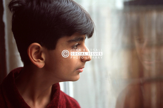 Portrait of teenage boy looking out of window,