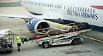 Baggage handler loading luggage onto British Airways plane at gatwick airport, London, England