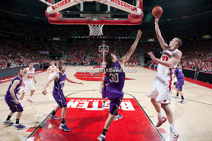 Wisconsin Badgers forward Jon Leuer (30) shoots the ball over the outstretched arm of Northwestern Wildcats forward Davide Curletti (30) during a Big Ten Conference NCAA men's college basketball game at the Kohl Center on February 27, 2011 in Madison, Wisconsin. Wisconsin won 78-63. (Photo by David Stluka)