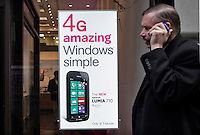 A man walks talking by phone next to a banner of the new Nokia Windows Smartphone Lumia 710 in a T-Mobile store in New York, United States. 11/01/12.  Photo by Kena Betancur / VIEWpress.
