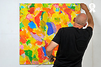 Painter  hanging frames on wall (Licence this image exclusively with Getty: http://www.gettyimages.com/detail/105765534 )