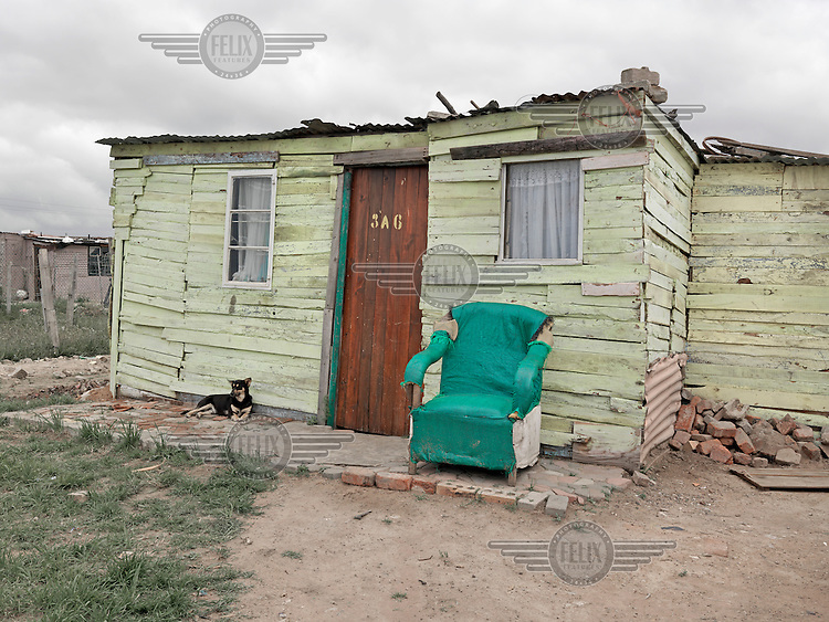 A dog rests outside a wooden shack neatly painted green. Graeme Williams' pictures of the environments occupied by some of South Africa's poorest people focus on the interiors and exteriors of people's homes, accentuating the minutiae of the occupants' day-to-day dwelling places. The bright colours captured in these photographs are suggestive of resilience, hope and a sense of humanity that survives in these poverty-stricken communities...