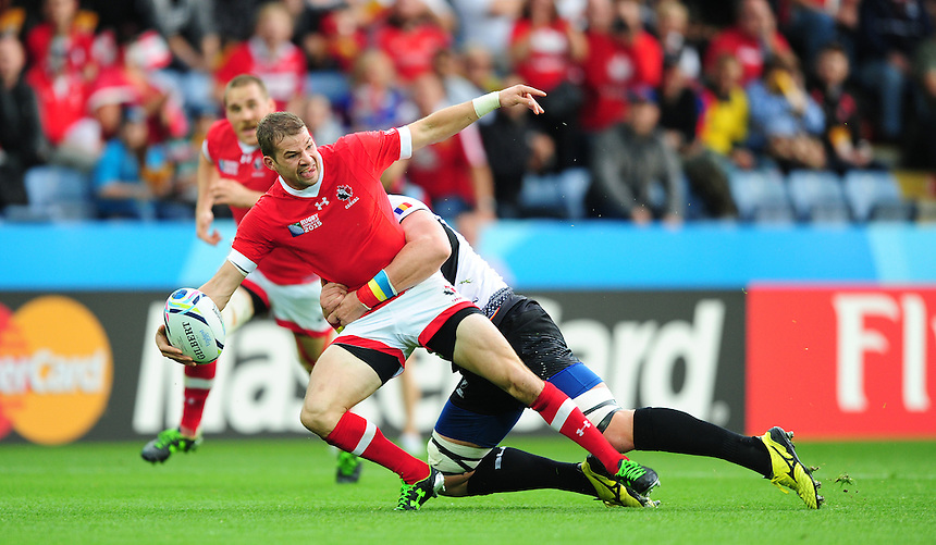 Canada's Gordon McRorie offloads the ball under pressure from Romania's Mihai Macovei<br /> <br /> Photographer Chris Vaughan/CameraSport<br /> <br /> Rugby Union - 2015 Rugby World Cup Pool D - Canada v Romania - Tue 6 October 2015 - King Power Stadium, Leicester <br /> <br /> &copy; CameraSport - 43 Linden Ave. Countesthorpe. Leicester. England. LE8 5PG - Tel: +44 (0) 116 277 4147 - admin@camerasport.com - www.camerasport.com