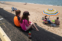 Charlott Crete (right), 9, and brother Andrew Crete, 6, eat snacks while sitting above their family on a recently-repaired portion of the parking lot embankment at Herring Cove Beach in the Cape Cod National Seashore outside of Provincetown, Mass., USA, on Fri., July 1, 2016. Portions of the parking lot have been closed after land eroded during storms earlier this year. The family is visiting Cape Cod from Saint-Sauveur, Quebec, Canada.