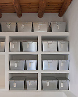 Simple zinc boxes are lined up on open stone shelving creating an effective storage system