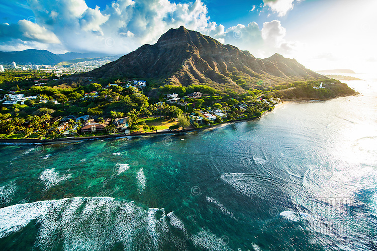 An aerial view of Diamond Head crested by hikers at sunrise, with waves rushing towards the beach, O'ahu.