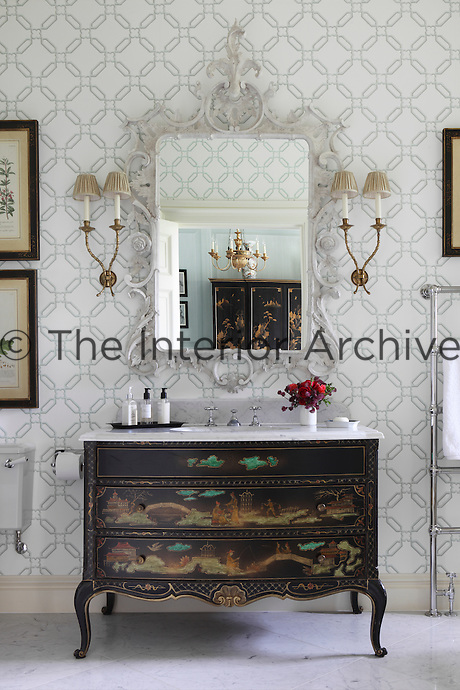 An ensuite bathroom furnished with a marble-topped washstand made of an antique chinoiserie chest of drawers