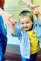 Young toddler boy holding mom's hands learning to walk.