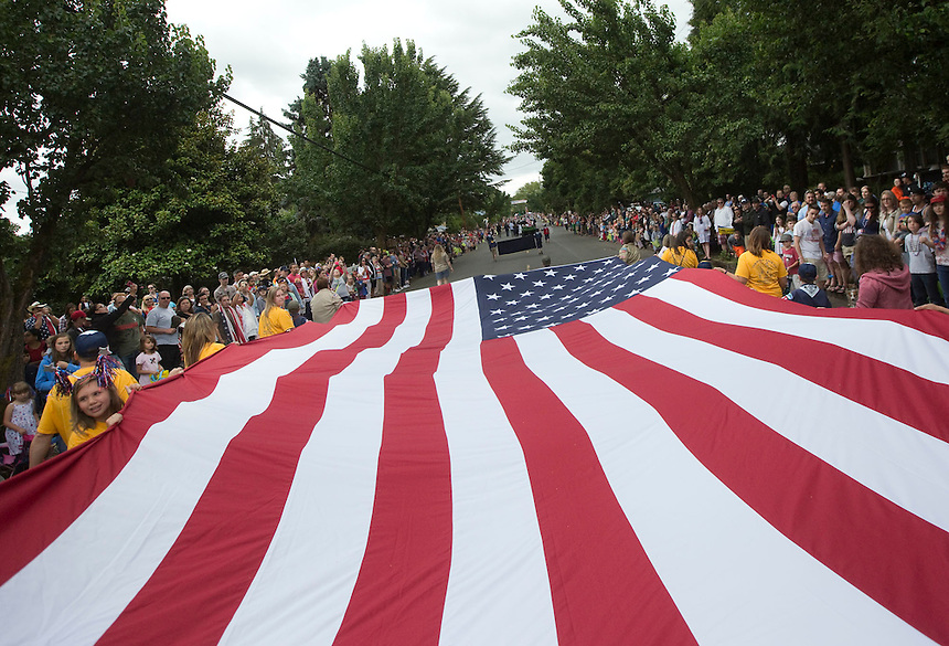 The Cub Scouts, pack 310, carry a giant flag, as they take part in the Fourth of July Parade in Ridgefield Monday July 4, 2016. (Photo by Natalie Behring/ for the The Columbian)