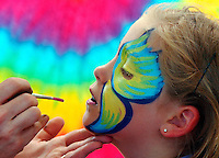 Brantley Smith, 7, of Anderson, closes her eyes as Tiffany Clark paints a butterfly on her face Monday at Freedom Weekend Aloft.