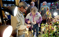 NWA Democrat-Gazette/DAVID GOTTSCHALK Paul Bowen (from left), of Rogers and Kathy Judy, of Elkins, fill out identification tags Friday, March 2, 2018, for their orchids display in the event center at the 8th annual Orchid Show and Sale at the Botanical Garden of the Ozarks in Fayetteville. Co-sponsored by the Orchid Society of the Ozarks and the Botanical Garden of the Ozarks, The indoor show began Friday and runs through Sunday featuring displays from different orchid societies, care mini-classes, a plant sale and a competition.