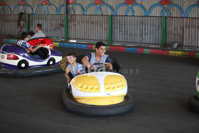 "Palestinians play at an amusement park during the fourth day of Eid al-Adha or ""Feast of the sacrifice"" in Gaza City on September 27, 2015. Muslims across the world are celebrating the annual festival of Eid al-Adha which marks the end of the Hajj pilgrimage to Mecca and is held in commemoration of Prophet Abraham's readiness to sacrifice his son to show obedience to God. Photo by Ashraf Amra"