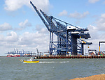 Small foot passenger ferry next to cranes at  Port of Felixstowe, Suffolk, England, UK