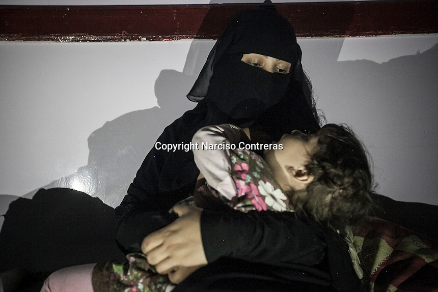 July 03, 2015 - Sana'a, Yemen: Khulud, a 28 years old woman, comforts her two years-old daughter in a classroom used as temporary shelter in Al Quds school in Sana'a. (Photo/Narciso Contreras)