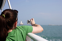 Tourist Mary Taylor takes a picture of the light house by Navy Pier while taking a tour boat ride on Lake Michigan in Chicago, Illinois on August 5, 2008.
