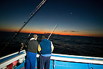 Two fishermen set a rod before the sun rises while Blue Fin Tuna fishing on the Gulf of St. Lawrence near North Rustico, Prince Edward Island, Canada.