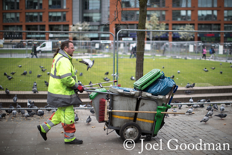 © Joel Goodman - 07973 332324 . 06/04/2017 . Manchester , UK . A street cleaner pushes his cart through pigeons in Manchester's Piccadilly Gardens . An epidemic of abuse of the drug spice by some of Manchester's homeless population , in plain sight , is causing users to experience psychosis and a zombie-like state and is daily being witnessed in the Piccadilly Gardens area of Manchester , drawing large resource from paramedic services in the city centre . Photo credit : Joel Goodman