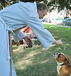 "Photo by Phil Grout..""Major"" receives the blessing of holy water from Father Ron Fisher during Ascension Church's.special Blessing of the Animals service."