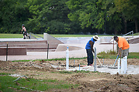 NWA Democrat-Gazette/J.T. WAMPLER Joshua Kinnard of Ft. Smith (LEFT) and Scott Brown of More OK. work Monday August 6, 2018 at the Splashpad at Walker Park in Fayetteville. The pad is located north of the skate park and west of the playground. The project will also include a new restroom facility.