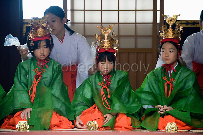 "Young ""yaotome"" female performers are cooled down with ice packs by maiko shrine attendants as they kneel in an antechamber during a ritual in the main hall of Tsurugaoka Hachimangu shrine during the second day of the 3-day Reitaisai grand festival in Kamakura, Japan on  15 Sept. 2012.  Photographer: Robert Gilhooly"