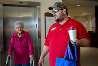 NWA Democrat-Gazette/JASON IVESTER --01/26/2015--<br /> Richard Embry with Hope Cancer Resources carries a bag and drink for patient Rowena Smith (left) as the pair head to his vehicle on Monday Jan. 26, 2015, at the Highlands Oncology Center in Rogers. Embry was transporting Smith to her Holiday Island home following treatment at the center.