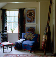 A small loveseat with a pretty embroidered loose cover sits in a corner of the bedroom