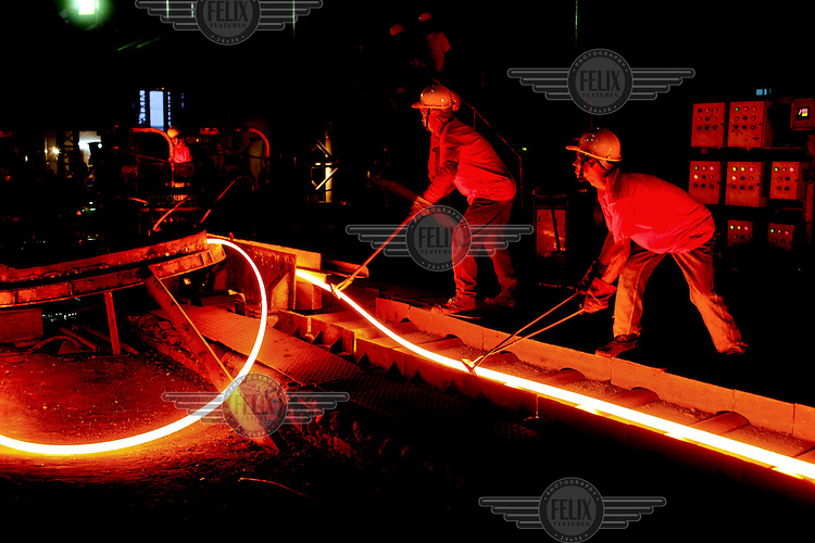 Workers monitor the making of new metal rods emerging glowing from a furnace at a steel recycling and re-rolling factory in Dhaka.