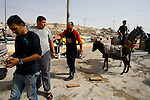 Scrap metal merchants from Al Khalil (Hebron) take payment from a satisfied customer in Al 'Eizariya (Bethany) near Jerusalem on 03/06/2010.