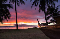 An outrigger canoe at rest on a Maui beach as the sun sets behind Lana'i.
