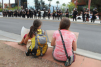 Phoenix, Arizona. April 25, 2012 - Once Phoenix Police finished arresting protesters and cleared Central Avenue between Palm Street and Montevista, two young women sit on the sidewalk holding signs and looking at police officers across the street. About 500 people protested the controversial law on the same day U.S. Supreme Court justices heard legal arguments on the Arizona vs. United States case. At the end of the march, six activists blocked Central Avenue by sitting in the middle of the street. They all were arrested by the Phoenix Police Department and taken to the Fourth Avenue County Jail. Photo by Eduardo Barraza © 2012