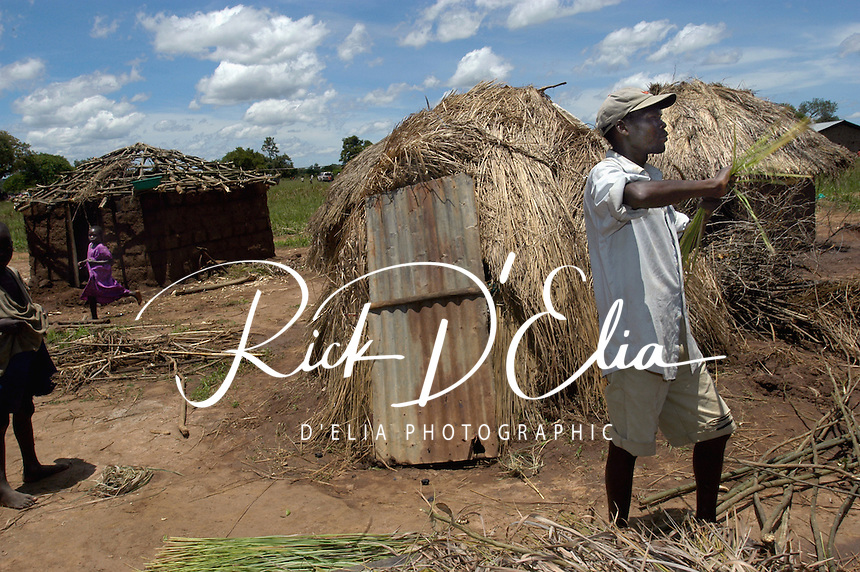 """David Ocuh constructs a """"strong hut"""", far left, to replace the less permanent structures he lives in with his wife and three children. He has lived in Abaku Camp 42 kilometers from Lira Town. The camp is home to 4,795 people. (Rick D'Elia)"""
