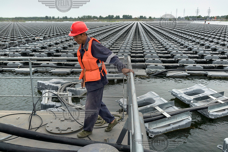 Yang Tuan Cheng, 57, a former coal miner who now works for the power company Sungrow, wires up an array of solar panels to an inverter. Each panel is attached to a buoy floating in a man-made lake created over a flooded coal mine.