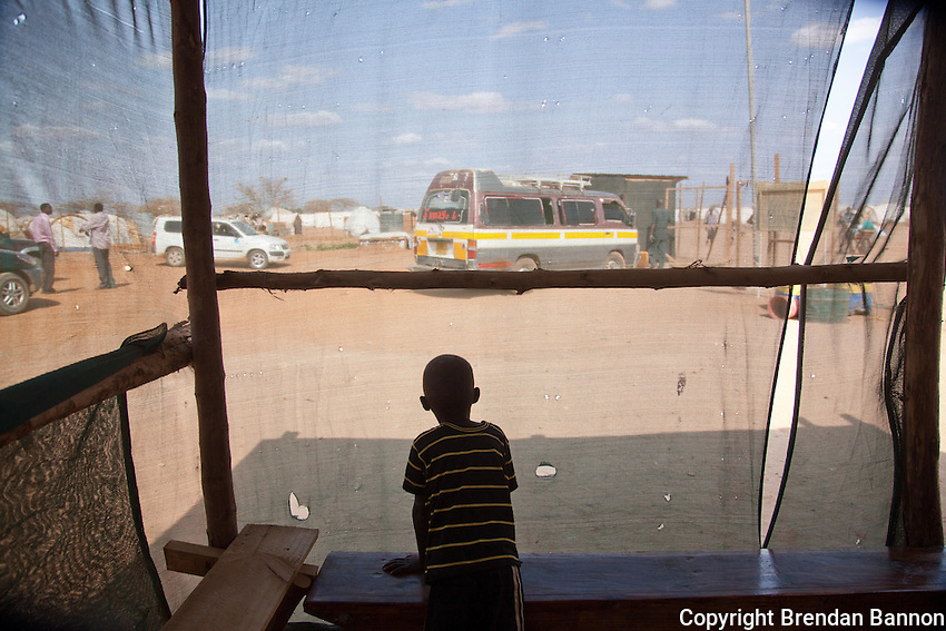 A refugee boy watching the busy parking lot of a MSF community medical clinic in Dadaab refugee camp in northern Kenya during one of the worst droughts in recent memory. The camp is host to nearly  400,000 refugees. Tens of thousands are coming each month as drought and continued war devastate communities.