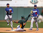 Dodgers shortstop Jerry Hairston throws over A's baserunner Brandon Allen turning a double play during a Cactus League preseason game between the Dodgers and the A's in Scottsdale, Ariz., on Wednesday, March 7, 2012.  Adam Kennedy is at right..Photo by Cathleen Allison