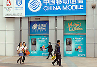 Pedestrians pass advertisement of China Mobile and Sony Ericsson in Nanning, China..