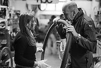 """Milano, quartiere Isola. La Ciclofficina Stecca Associazione +bc. Un meccanico aiuta una ragazza a riparare la camera d'aria forata --- Milan, Isola district. """"Stecca"""" bicycle cooperative at the +bc association. A mechanic helping a girl to repair the punctured tube"""