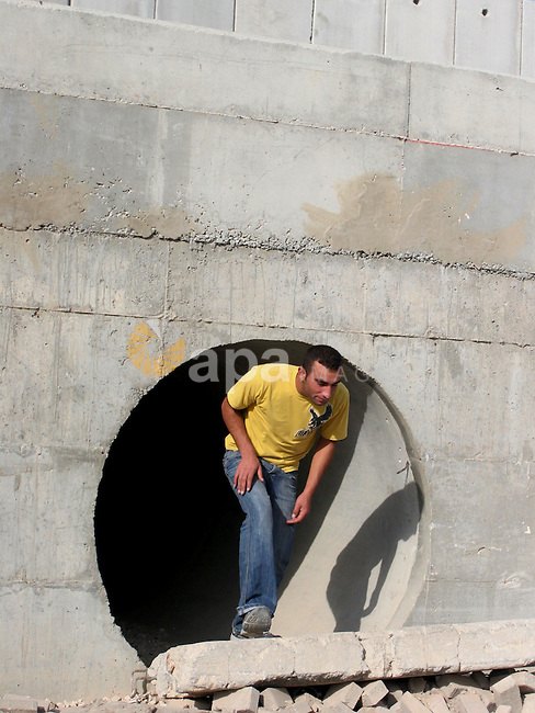 A Palestinian young man uses a spillway to bypass the Israeli built controversial separation barrier in the al-Ram, northern of Jerusalem city. The spillway is used by Palestinians to cross the separation barrier when the Israeli Army closes the access gates of the wall.