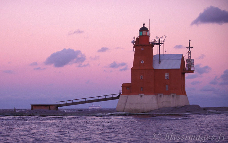 Porkkala (Kallbådan) Lighthouse bridges Silja Line passing in the Gulf of Finland at sunset.