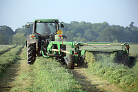 Farmer and tractor mowing grass for hay and haylage production