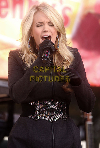 "CARRIE UNDERWOOD.Carrie Underwood performs on ABC's ""Good Morning America"" at the Lincoln Center for the Performing Arts, New York, NY, USA..November 3rd, 2009.stage concert live gig performance performing music black grey gray coat jacket belt leather gloves microphone half length singing .CAP/ADM/AC.©Alex Cole/AdMedia/Capital Pictures."