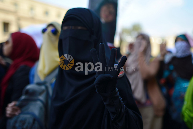 An Egyptian student who support Muslim Brotherhood and ousted President Mohammed Morsi, flashes Rabaa sign during a demonstration demanding for release her fellow Radwa Jamal, who was arrested by Egyptian police, at Cairo University on November 5, 2014. Photo by Amr Sayed