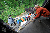 Conductor Charles Baldwin, center, helps Frannie Christensen and John Lovert unload their rafting gear at Gold Creek. The couple was planning to float the Susitna River to Talkeetna. The Alaska Railroad's Hurricane Turn is one of America's last true whistlestop trains.