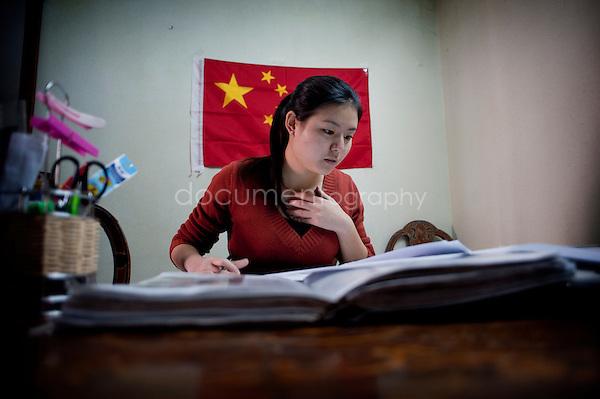 Copyright : Magali Corouge / Documentography.Le Caire, le 26 janvier 2013. .Yitong Shen dans le salon de son appartement du quartier d'Abbasseya du Caire. Derriere elle le drapeau de la Chine.